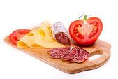 Salám, sýr a rajče na dřevěné desce izolovaných na bílém
