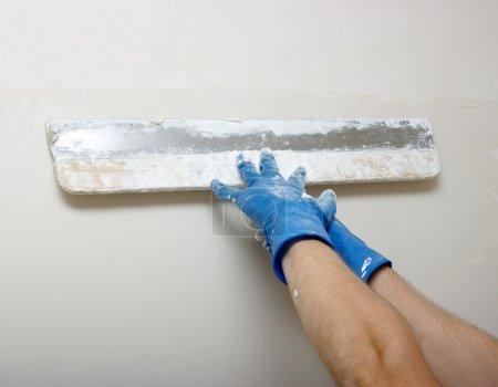 Photo pour Maître fait du plâtre sur un mur - image libre de droit
