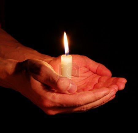 Photo pour Brûlage de la bougie dans une main dans les ténèbres - image libre de droit