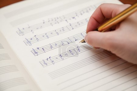 Hand with pen and music sheet