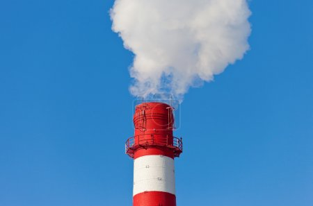 Industrial chimney with smoke over blue sky