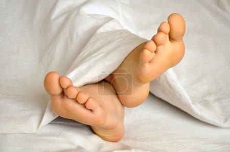 Photo pour Dormir adolescent fille pieds sous la couverture - image libre de droit