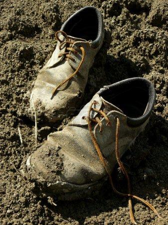 Photo pour Chaussures usées boueuses dans la saleté - image libre de droit