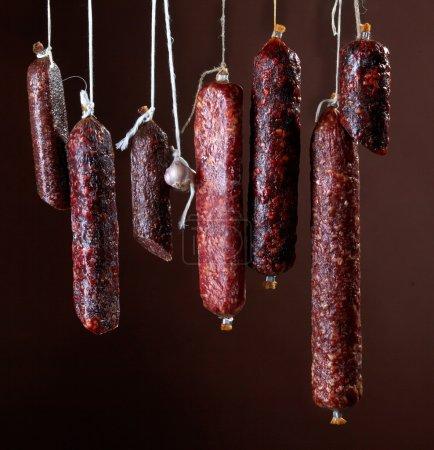 Photo pour Différentes saucisses de salami suspendues - image libre de droit
