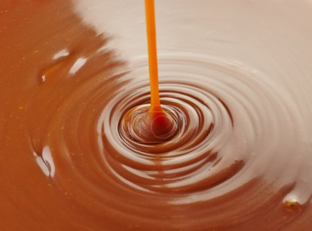 Pouring sweet caramel sauce on caramel background...