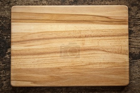 Photo for Top view of wooden cutting board on old wooden table - Royalty Free Image