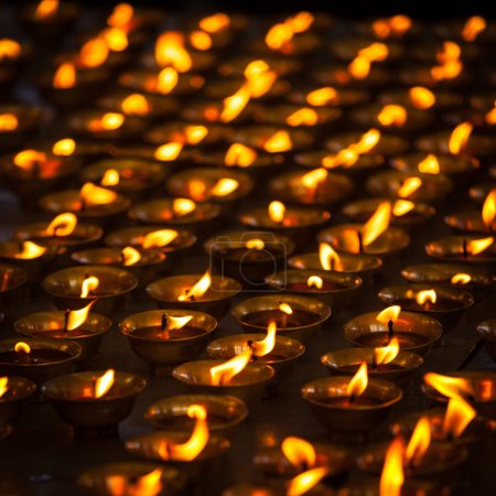 Burning candles in Buddhist temple. Tsuglagkhang c...