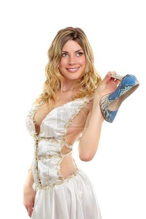 Photo pour Blonde souriante sexy portant une robe de mariée blanche et tenant sa chaussure. Isolé - image libre de droit