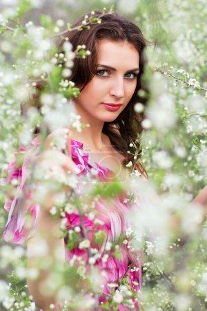 Foto de Retrato de la joven y guapa morena posando en árboles que florecen - Imagen libre de derechos
