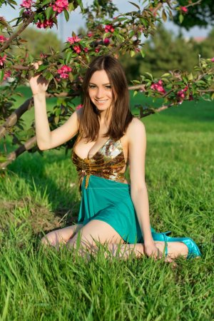 Photo for Young smiling woman sitting on the grass near a flowering tree - Royalty Free Image