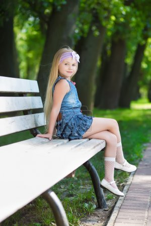Photo for Blond little girl sitting on the white bench - Royalty Free Image