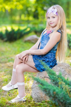 Photo for Beautiful little girl sitting on the stone outdoors - Royalty Free Image