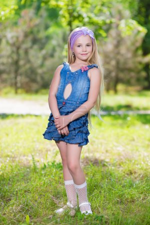 Little blond girl in jeans dress
