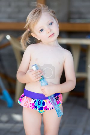 Little blond girl in water pool