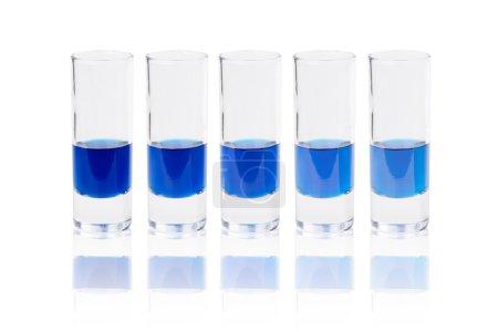 Six glasses with blue liquid