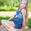 Little girl in blue jeans dress sitting on the sto...
