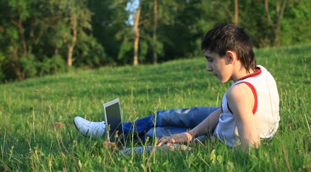 Teenager with laptop resting on meadow