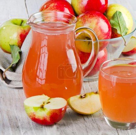 Photo pour Jus de pomme et pommes sur table en bois. Concentration sélective - image libre de droit