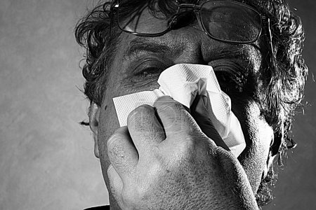 Middle-aged man blowing his nose into a tissue, black and white