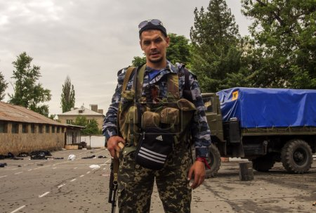 Pro-Russian armed man near an entrance to a border guards base