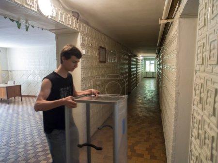 Photo pour Un jeune homme ensembles urnes décorées avec les armoiries de l'ukraine, dans le Bureau de vote--le dimanche 11 mai de Lougansk est prévu d'organiser un référendum sur l'autodétermination de la région. - image libre de droit