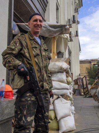 Photo pour Garde armé devant le bâtiment de militants pro-russe. République autoproclamée Louhansk nommé des élections présidentielles dans la région de luhansk illégale. - image libre de droit