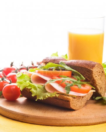 Photo for Sandwich with ham, tomato, lattuce and arugula with glass of orange juice with copy space. - Royalty Free Image