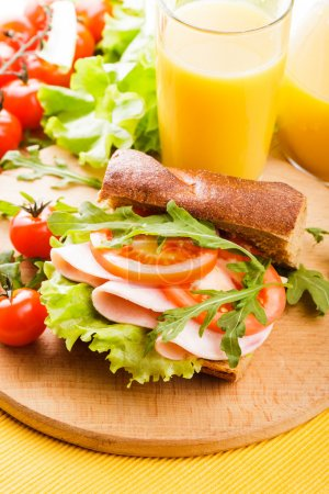 Photo for Wholegrain sandwich with ham, tomato, lattuce and arugula with glass of orange juice on the board - Royalty Free Image