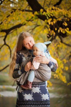 Photo pour Mère marchant avec bébé en fronde dans le parc - image libre de droit