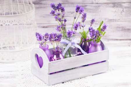 Photo for Lavender in bottles, decor provance style, wooden box and birdcage on crochet tablecloth - Royalty Free Image