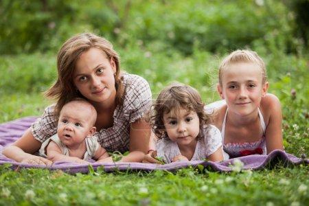 Photo pour Bonne famille sur l'herbe verte dans le jardin - image libre de droit