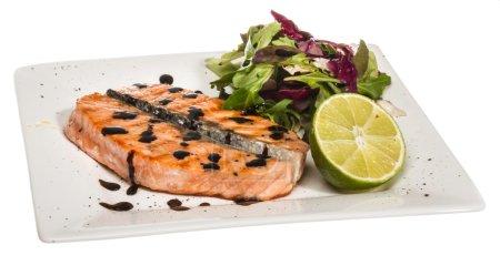 Photo pour Portion de poisson salé : filet de saumon nordique rôti garni de feuilles de salade et de basilic et de citron vert sur un plat blanc isolé à la saucisse balsamique - image libre de droit