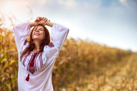 Photo pour Portrait d'une jeune femme en chemise ukrainienne traditionnelle debout avec champ de maïs sur le fond - image libre de droit