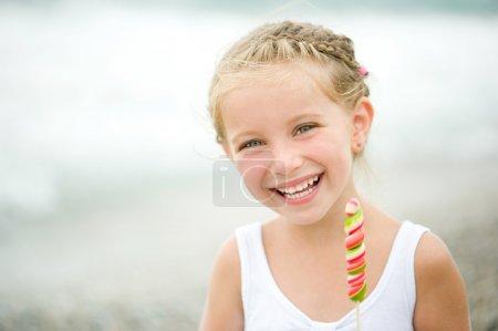 Photo pour Adorable petite fille avec un bonbon sur la plage tropicale vacances - image libre de droit