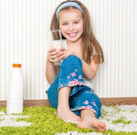 Photo pour Petite fille de smiley boire le lait sur le sol dans sa maison - image libre de droit