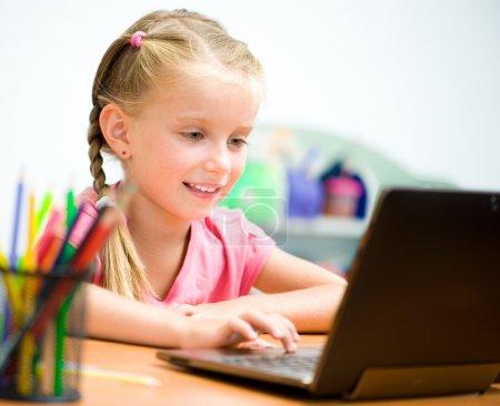 Photo pour La fille fait des exercices sur un ordinateur portable - image libre de droit