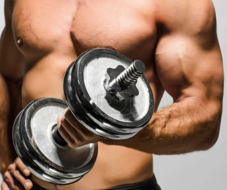 Photo for Handsome muscular man working out with dumbbells - Royalty Free Image