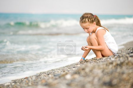 Photo for Girl with pebbles on the beach - Royalty Free Image
