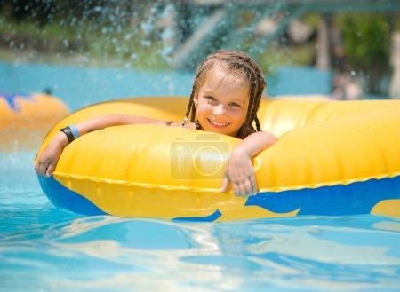 Photo pour Petite fille mignonne assise sur un anneau gonflable dans la piscine . - image libre de droit