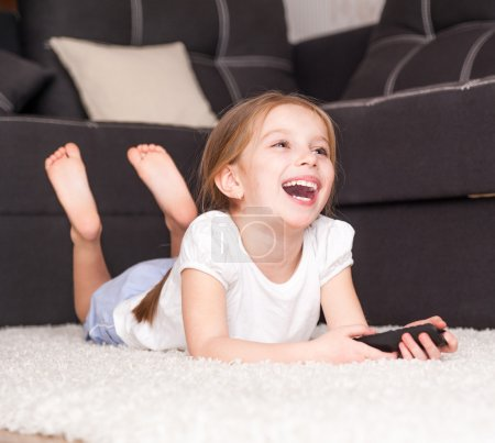 Photo pour Heureuse petite fille mignonne tenant une télécommande - image libre de droit