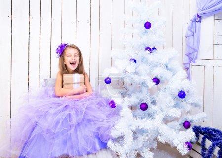 Photo pour Petite fille souriante avec un cadeau dans les mains près de l'arbre de Noël - image libre de droit