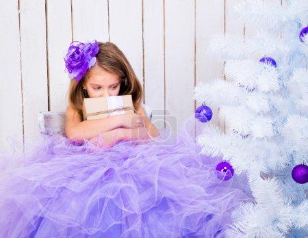 Photo pour Triste petite fille avec un cadeau dans les mains près de sapin de Noël blanc - image libre de droit