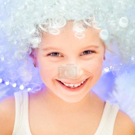 Photo pour Belle petite fille dans une perruque blanche près du sapin de Noël - image libre de droit
