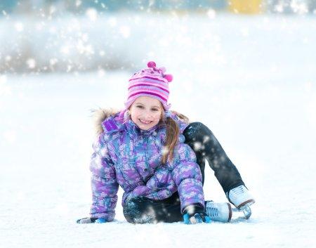 Photo pour Joyeuse petite fille assise sur la glace en hiver à l'extérieur - image libre de droit