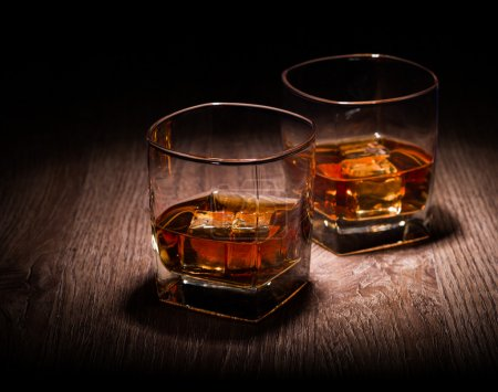 Photo for Whiskey in glasses on wooden table - Royalty Free Image