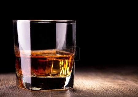 Photo for Glass with whiskey on wooden table - Royalty Free Image