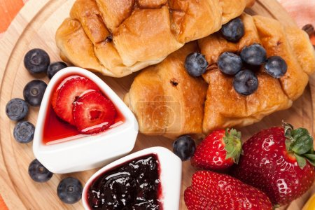 Photo for Breakfast with croissant, toasts, jam and fruits - Royalty Free Image