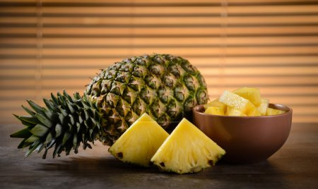 Photo for Ripe pineapple cut into slices on wooden table - Royalty Free Image