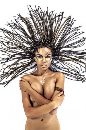 Portrait of a beautiful naked young african american woman with dreadlocks hair lying on a white background