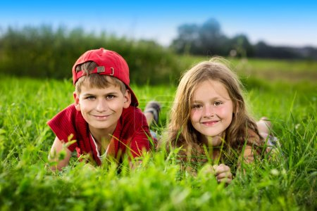 Cut boy and a girl are resting on the green grass in summer